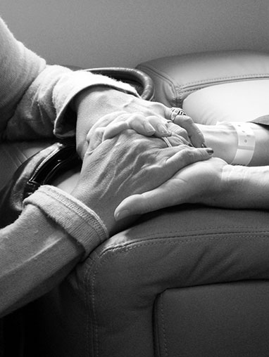 Nurse holding hands with an elderly patient